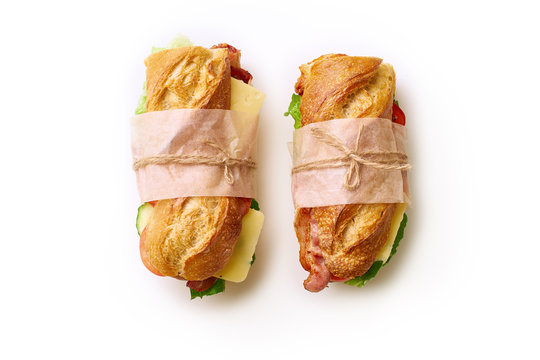 Two fresh big baguette sandwiches with bacon, chedder cheese, mustard, lettuce and vegetables isolated on white background