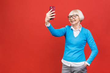 It's selfie time! Image of cheerful mature old woman standing isolated over red background wall talking by mobile phone.
