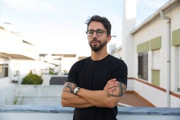 Confident stylish guy with tattoos posing on apartment balcony or terrace. Young man in glasses standing outside with arms crossed and looking at camera. Male portrait concept Fotomurales