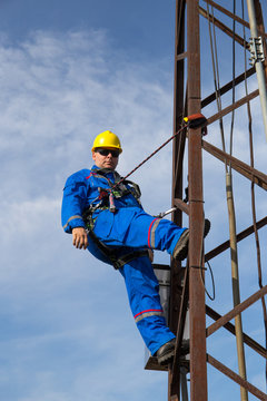 Electrician with yellow helmet and safety belt climbs the pole