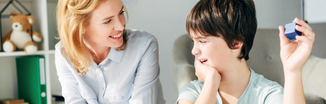panoramic shot of smiling child psychologist looking at kid with dyslexia