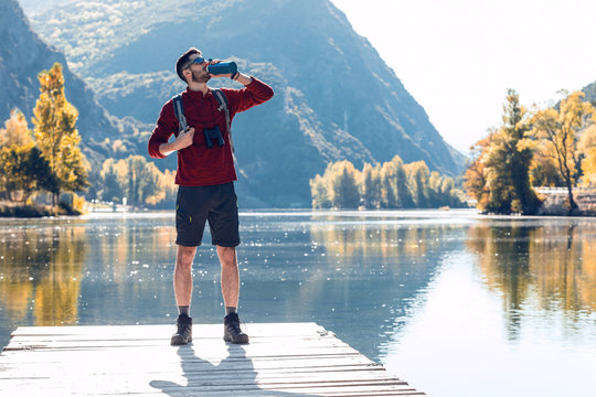 Hiker young man traveler with backpack drinking water while standing in front of lake.