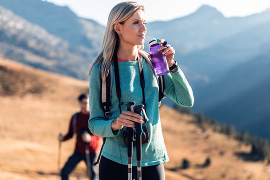 Pretty young woman traveler with backpack looking to the side while drinking water on mountain.