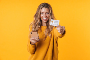 Image of charming blonde woman holding credit card and cellphone