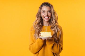 Image of joyful woman smiling and holding birthday cake with candle