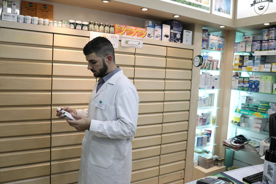 Pharmacist Ilias Grammatikakis holds hemp oil drops, in his pharmacy in Athens