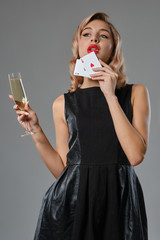 Blonde girl in black dress holding two playing cards and glass of champagne, posing against gray background. Gambling, poker, casino. Close-up.