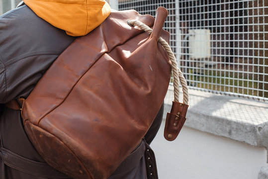 Man travel with leather backpack, close up. Urban style, street fashion. Fashion man with luggage, back view