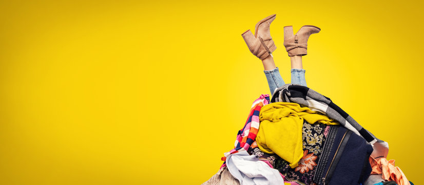 woman legs out of clothes pile on yellow background with copy space