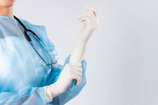 Female doctor surgeon preparing for the surgical operation, she is wearing gloves and scrubs, healthcare and preparation concept. Young doctor putting on rubber gloves in clinic close up