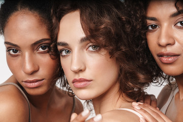 Close up beauty portrait of three attractive young sensual multiethnic women