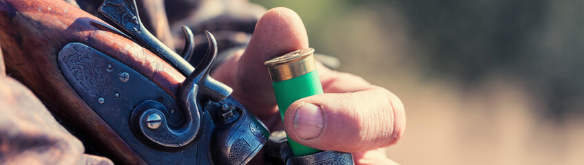 Close up of hunter loading shotgun. Holds a gun and ammunition in his hand.