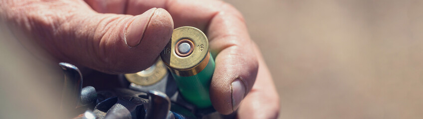 Close up of hunter loading shotgun, .holds a gun and ammunition in his hand.