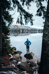 Foto op Canvas Ontspanning Young man standing alone an staring at lake. Foggy air. Early chilly morning in winter.