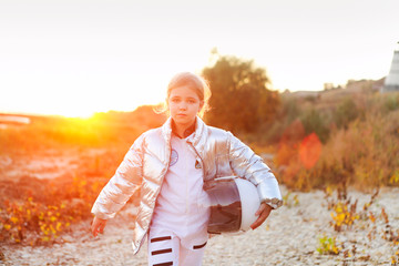 Astronaut futuristic kid girl with white full length uniform and helmet wearing silver shoes...