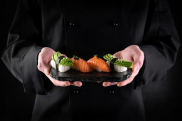 Aluminium Prints Sushi bar Sushi served on stone slate in chef hands on dark background. Decorated sashimi nigiri with salmon and avocado. Traditional japanese food. Copy space for text