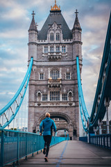 Runner in the morning training on the Tower Bridge in London. Sport in City, concept photo
