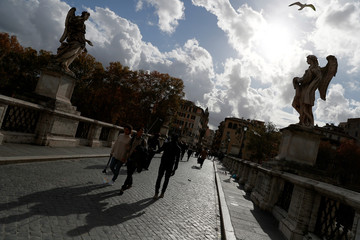 People walk across the Ponte Sant'Angelo on an autumnal day in Rome
