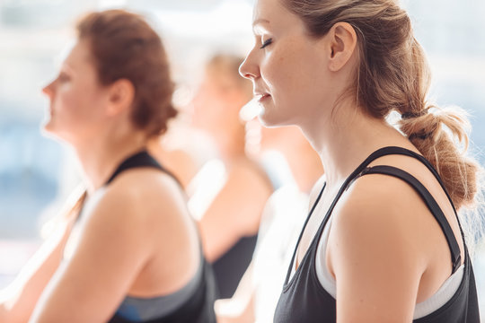 Group yoga classes young woman meditate in the lotus position on the background of people lying in shavasana pose on the floor in the gym with a large window. Concept of peace and spirituality