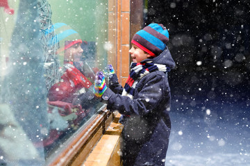 Cute little healthy school kid boy on Christmas market. Funny happy child in fashion winter clothes making window shopping decorated with gifts, xmas tree. Snow falling down, snowfall
