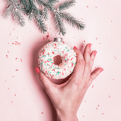 Fototapete - Female hand hangs Christmas bauble made of glazed donut on pink background. Christmas creative concept
