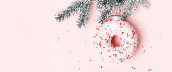 Wall Mural - Christmas toy donut with sugar sprinkling hanging on Christmas tree branch, banner format