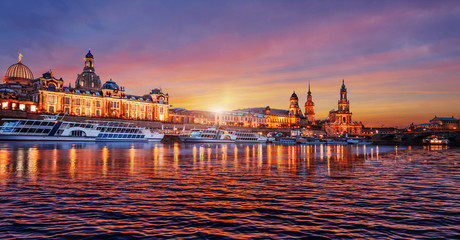Wonderful colorful sunset over the famouse Old Town architecture in Dresden, with Elbe river embankment with reflections. Colorful sunset  in Dresden, Saxony, Germany, Europe. Creative image.