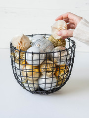 A metal wicker basket with various Christmas balls and a female hand taking