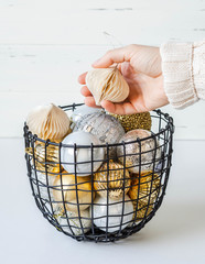 A metal wicker basket with various Christmas balls and a female hand taking toy