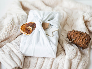 Fabric wrapped gift with paper tag, dry orange slice and ceramic star. Reusable sustainable gift wrapping alternative.