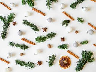 Flat lay creative Christmas vibrant composition with fir branches, Christmas decorations and spices on a white background. Top view