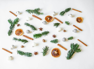 Flat lay creative Christmas vibrant composition with fir branches, Christmas decorations and spices on white background.