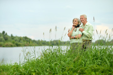 Portrait of happy senior woman and man by lake