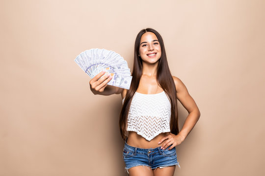 Portrait of playful beautiful woman holding bumch of money isolated over beige background