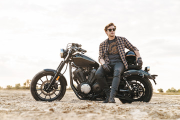 Man biker on bike outdoors at the desert field. Wall mural