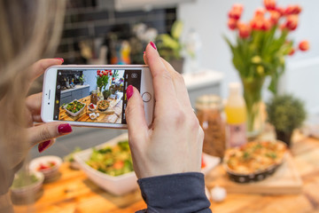 Woman with red nails shooting photos of food on a household table with her mobile phone for social media instagram healthy diet high protein food for a great body and lifestyle table flowers bread