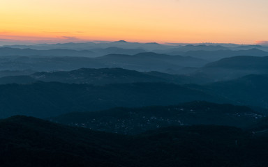 Wall Mural - Panorama of a mountain landscape at sunset. Hills blue gradient background. Orange sky on the horizon. Misty evening in the mountains.