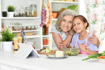 Portrait of cute little girl with her grandmother cooking together at kitchen table