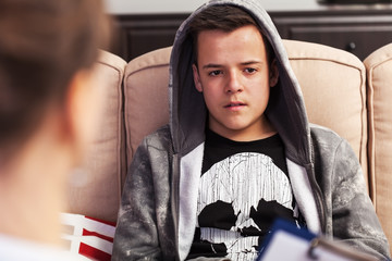 Obraz Teenager boy sitting at counseling - in front of the therapy professional, close up - fototapety do salonu