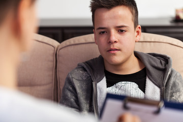 Young teenager boy at counseling - talking to the therapy professional, close up