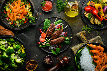 Set of food and dishes of vegetables, meat and fish on wooden background. Top view. Free space for your text.