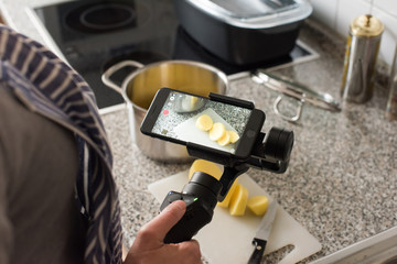 Blogger making smartphone video while cooking