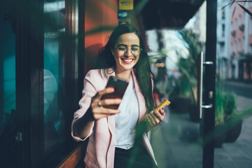 Happy Spanish woman in casual wear clicking selfie pictures via front camera on cellphone gadget, positive cheerful hipster girl smiling at camera for taking photos of herself enjoying free time