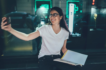 Cheerful Spanish hipster girl in optical spectacles enjoying free time for clicking selfie pictures with cellphone application, happy woman in glasses holding knowledge textbook and smiling at camera