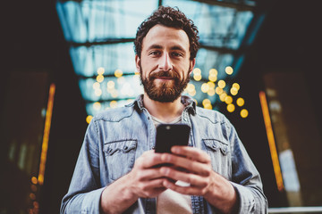 Half length portrait of handsome caucasian bearded guy holding mobile phone connected to 4G for blogging, casually dressed male hipster using modern smartphone outdoors satisfied with updates. Fotobehang