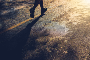A lonely runner trains on wet asphalt at sunset, copy space.