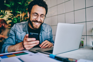 Obraz Positive caucasian hipster guy in eyewear laughing at content from social networks using mobile phone for browsing, cheerful male freelancer having fun during remote job  chatting on cellular. - fototapety do salonu