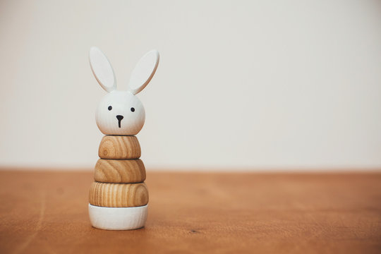 Stylish wooden toy for child on wooden table. Modern  wooden bunny pyramid with rings. Eco friendly, plastic free toys for toddler. Space for text