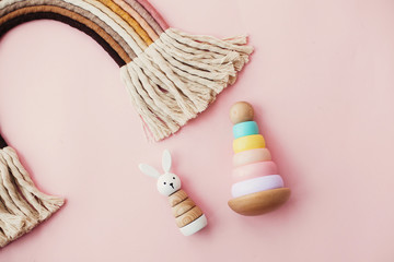 Eco friendly plastic free toys for toddler. Stylish wooden toys for child on pink background. Modern colorful wooden pyramid with rings, wooden bunny and macrame rainbow.