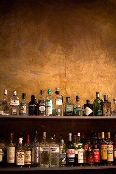 Bar shelves full of alcoholic beverages bottles